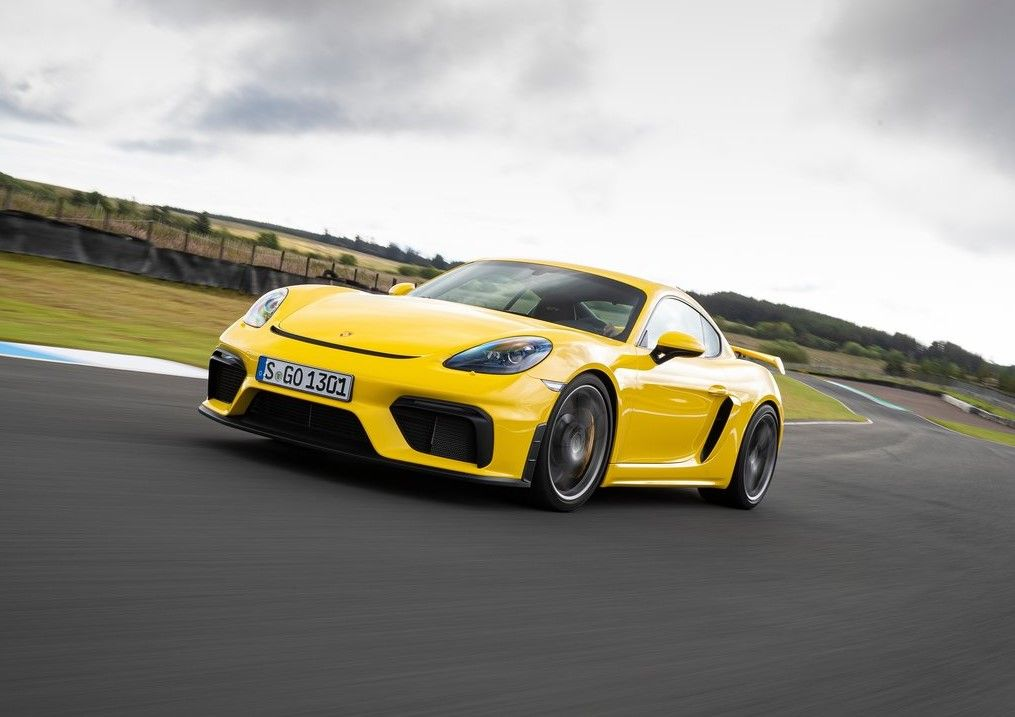 yellow 2020 Porsche 718 Cayman GT4 front three angle track racing